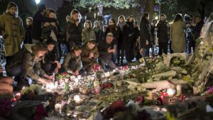 epa05025819 People pray, place flowers and light candles in tribute for the victims of the 13 November Paris attacks near the Bataclan concert venue in Paris, France, 14 November 2015. At least 129 people were killed in a series of attacks in Paris on 13 November, according to French officials. EPA/IAN LANGSDON